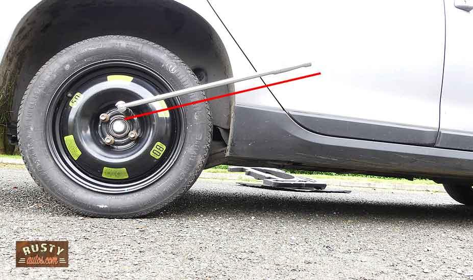 Lug nut wrench on car wheel
